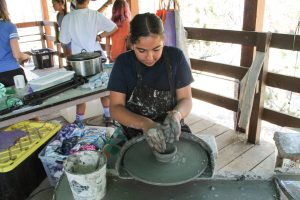 A camper works on a ceramic wheel at a summer camp arts and crafts program