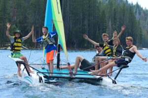 Campers sail on a large Hobie Catamaran Sailboat at Gold Arrow Camp
