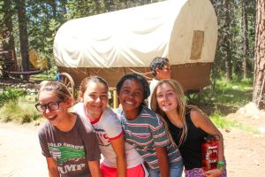 Smiling campers pose at a summer camp in front of a covered wagon