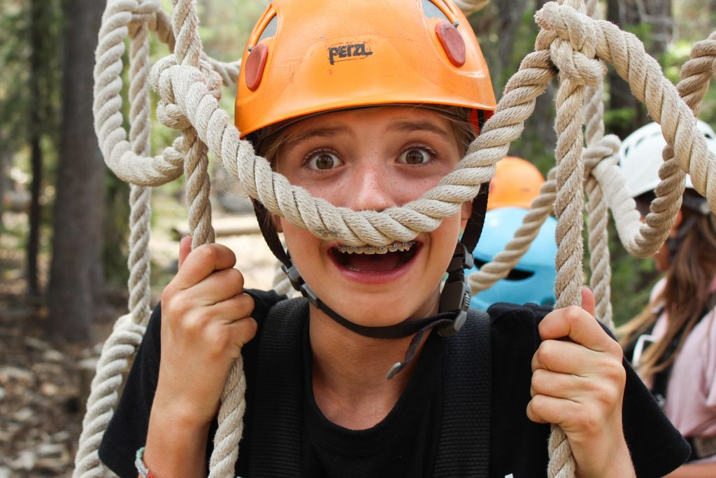 A camper smiles happily at summer camp while looking through a cargo net