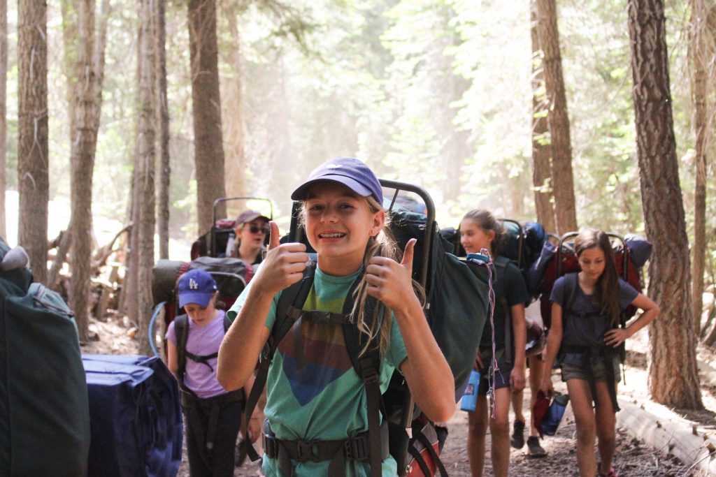 A summer camp camper gives two thumbs up on a backpacking trip