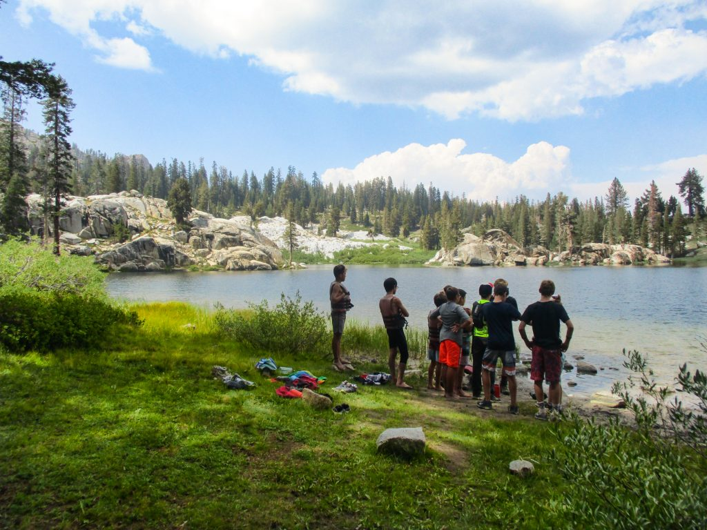 A group of backpackers looks at a mountain lake in the high sierra