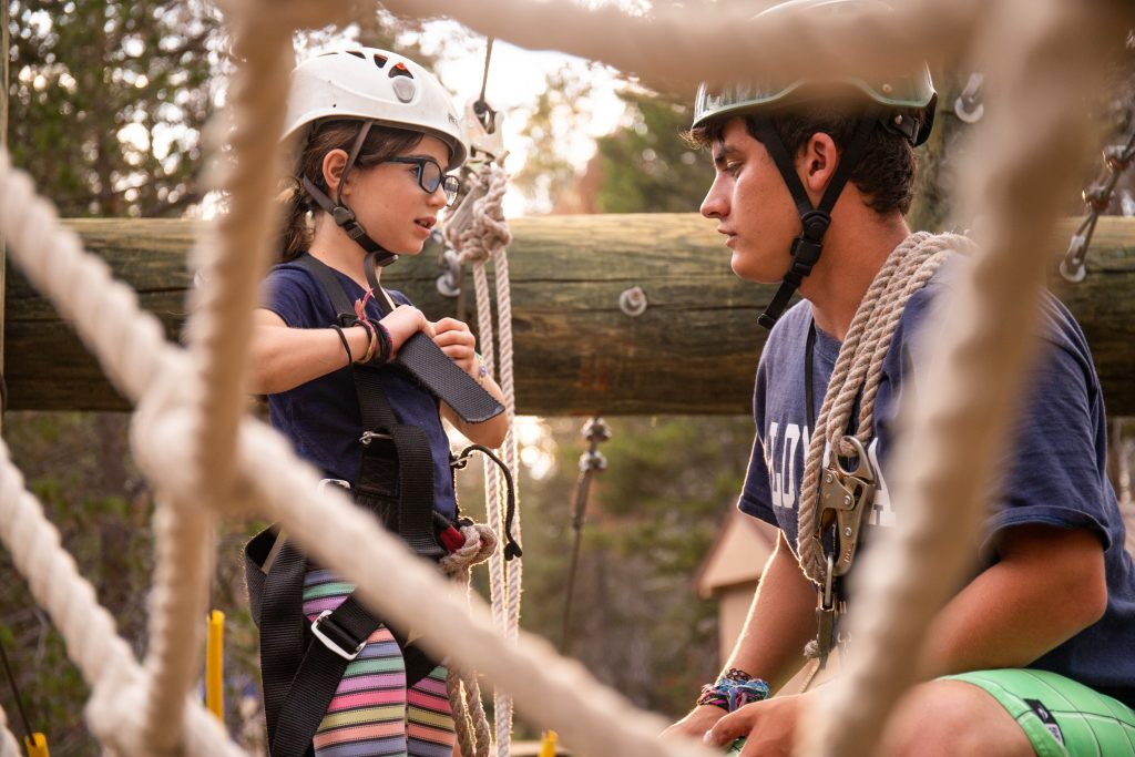 Summer Camp staff member at Gold Arrow Camp prepares a young girl to climb a cargo net