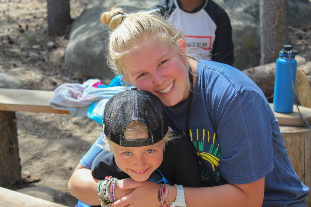 Summer Camp counselor smiles at camera while hugging camper
