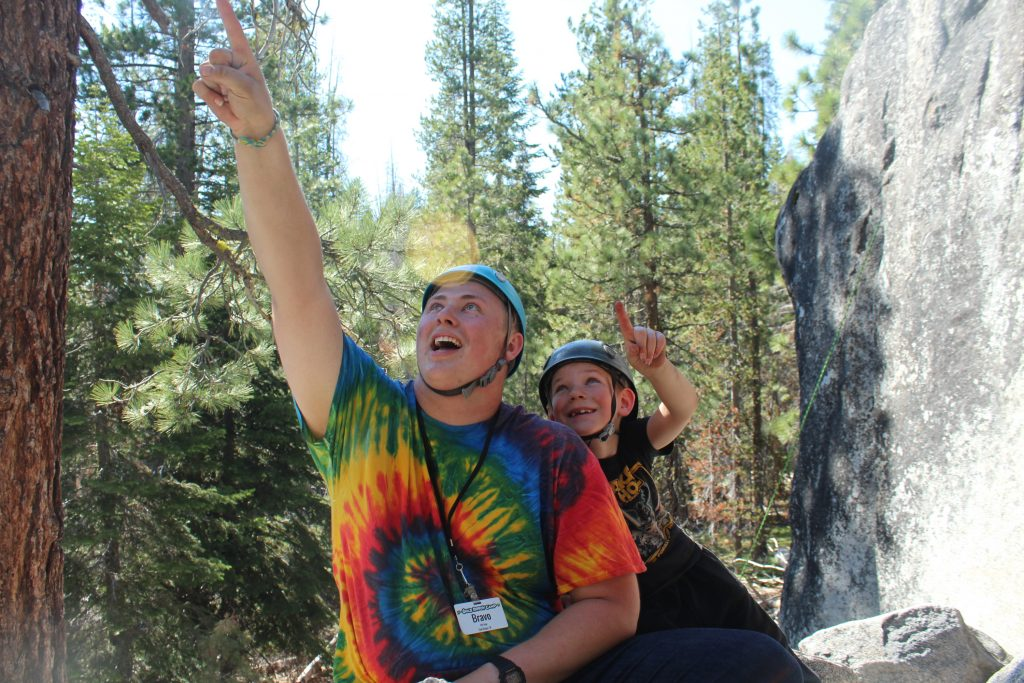 Summer Camp staff member at Gold Arrow Camp in a tie dye shirt points at the sky while a young boy points along with him
