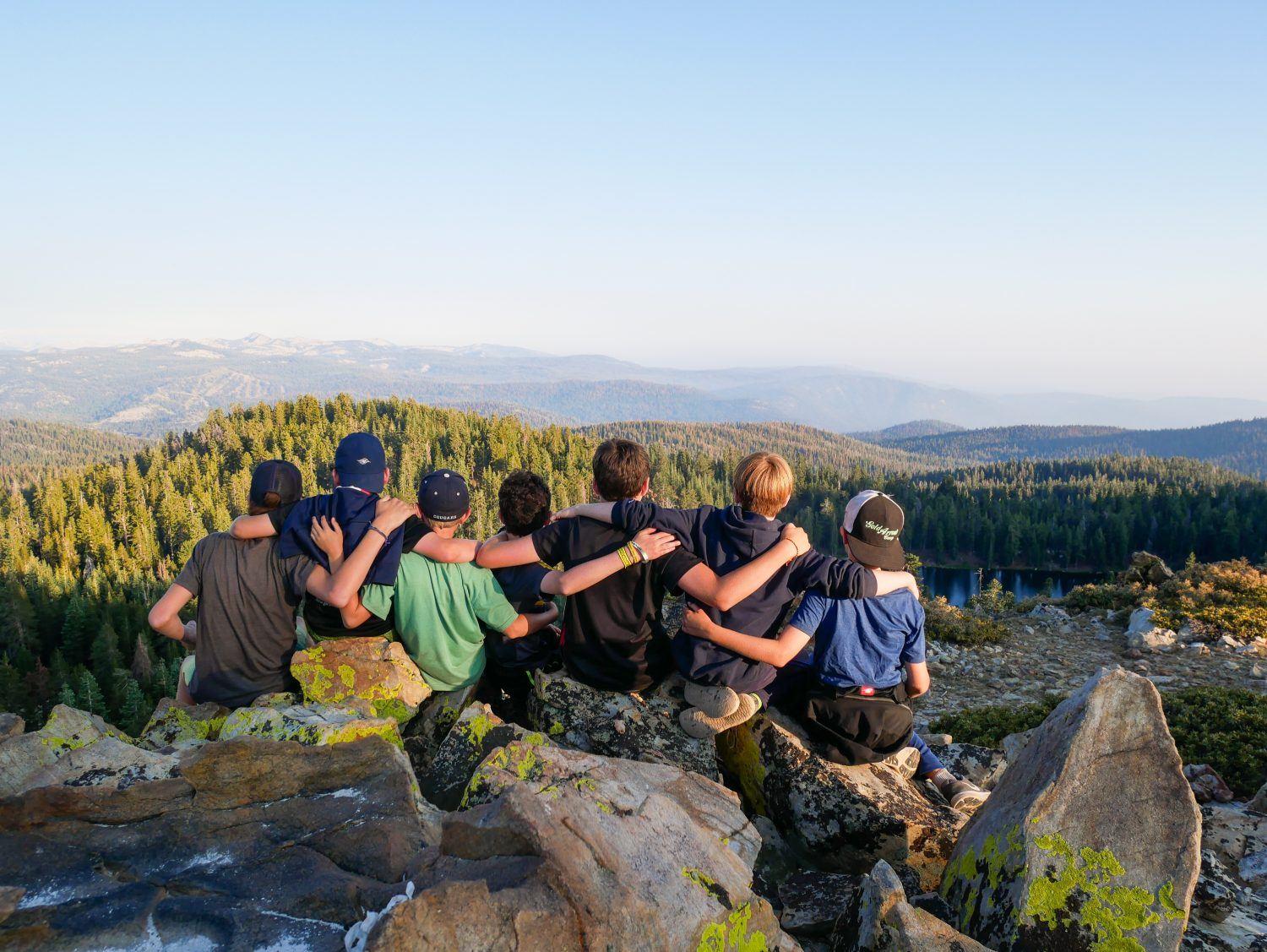 Campers at a summer camp have their arms over each other's shoulders while they look out over the Sierra Nevada and a mountain lake