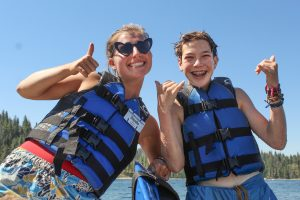 A counselor and a camper at a summer camp in California on Shaver Lake both smile with thumbs up
