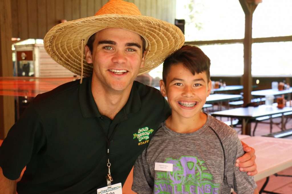 A male camp counselor with his arm around a camper at Gold Arrow Camp
