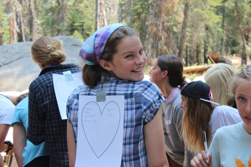 A girl at a summer camp in California smiles at the camera with a heart taped to her back