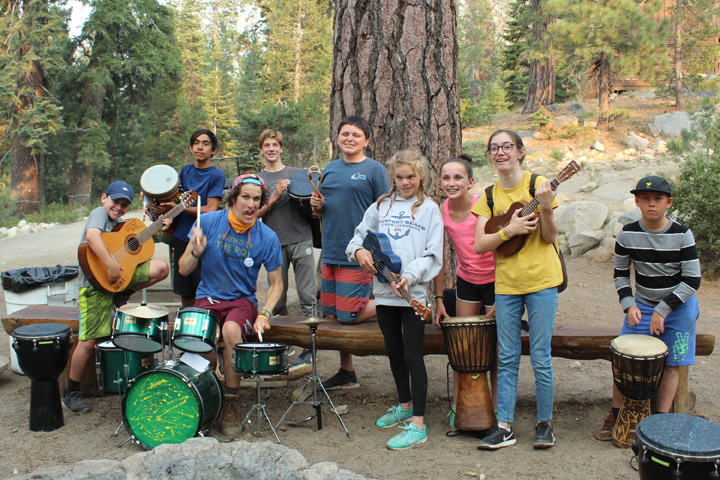 Campers and a counselor play guitars and drums at a summer camp in California