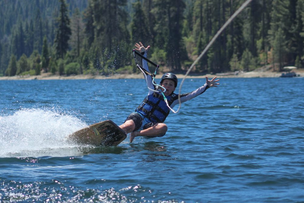 A boy falls from a wake skate while at a summer camp on Shaver Lake in California