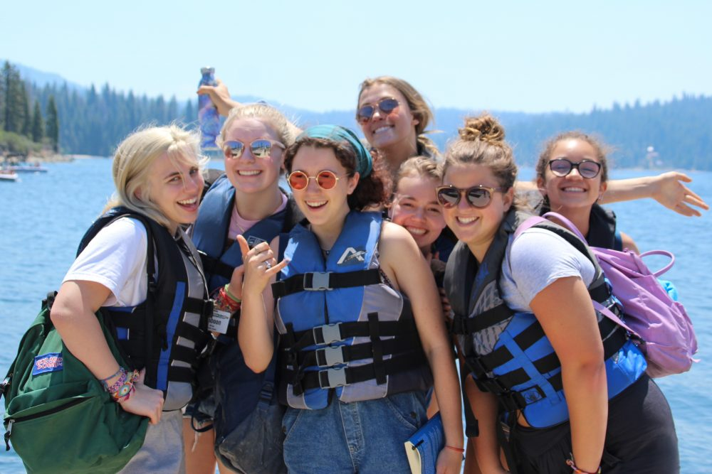 Group of teen girls in lifejackets at Shaver Lake at a summer camp in California