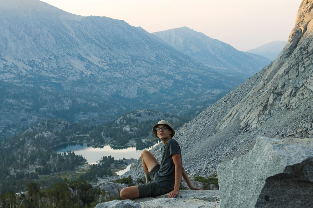 A teen boy sits on the edge of a mountain overlooking a lake in the High Sierra of California