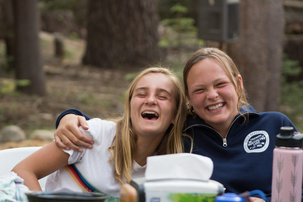 Two girls laugh at a table at a summer camp in California