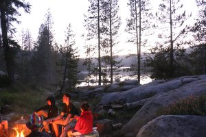 Campers gather around a campfire with a mountain lake in the background