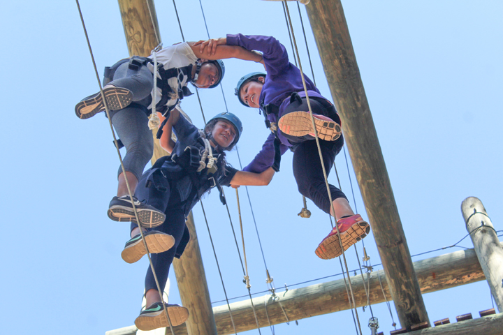Campers work together to cross a high ropes course at Gold Arrow Camp in California