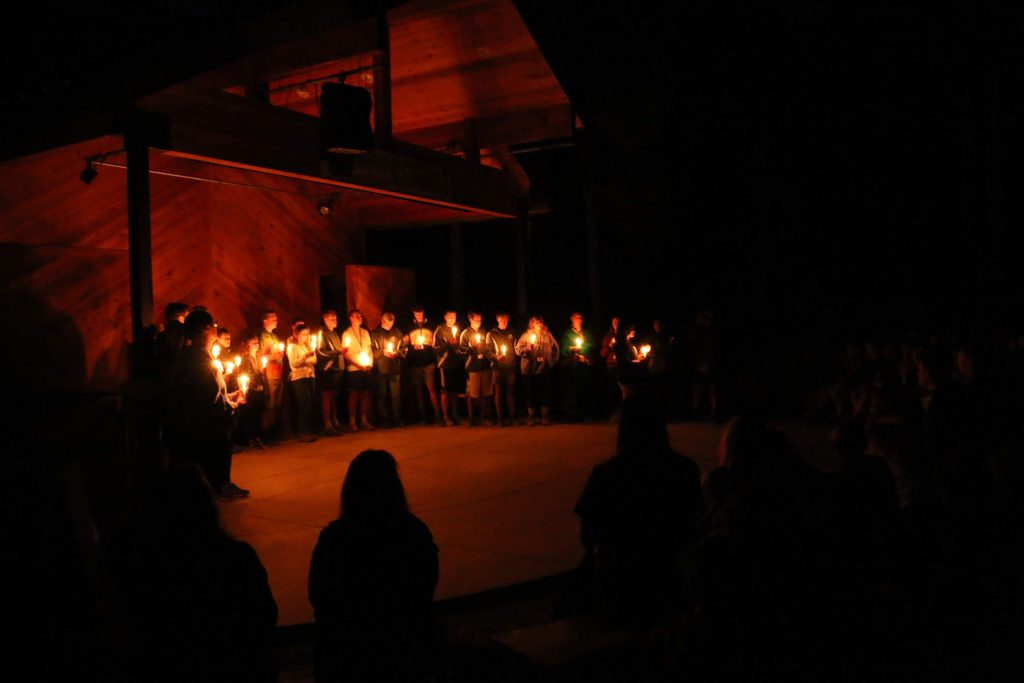 Counselors at Gold Arrow Camp, a summer camp in California, light candles to show their appreciation for their campers