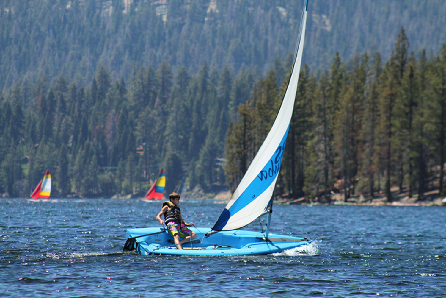 A camper sails an RS Q'ba on Huntington Lake California at Gold Arrow Camp