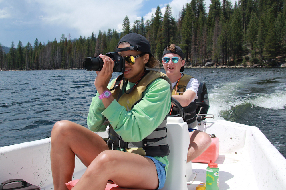 A photographer takes summer camp photos on a boat at a children's summer camp in California