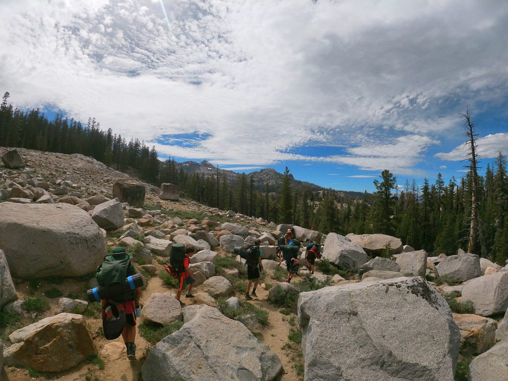 Campers backpack through a rock field under a bright blue sky at Gold Arrow Camp